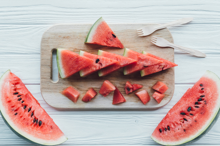 flat lay with arranged watermelon pieces on cutting board and plastic cutlery on wooden tabletop