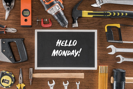 top view of blackboard with lettering hello monday near arranged various tools on wooden table
