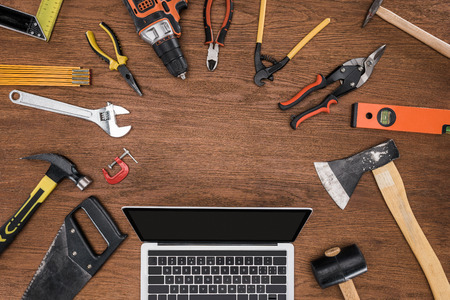 top view of laptop with blank screen surrounded by arranged various tools on wooden table
