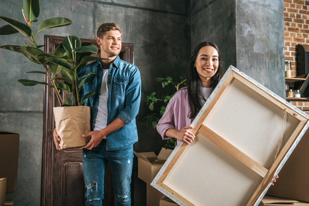 happy young woman carrying canvas and her boyfriend holding ficus plant while moving into new home