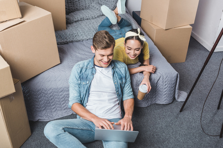 high angle view of happy young couple in bedroom using laptop while moving into new home