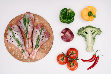 top view of raw turkey legs with rosemary on cutting board with different vegetables near, isolated on white