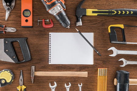top view of empty textbook surrounded by arranged various tools on wooden table