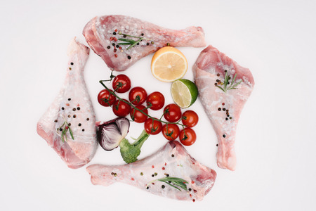 top view of turkey legs with cherry tomatoes, lime and lemon, isolated on white