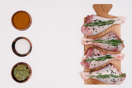 top view of raw chicken legs with rosemary on wooden board with salt, paprika and bay leaves in bowls, isolated on white Stock Photo