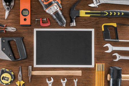 top view of empty blackboard near arranged various tools on wooden table Stock Photo