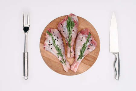 top view of raw turkey legs with pepper corns and rosemary on cutting board with fork and knife, isolated on white