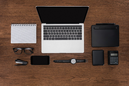 top view of workplace with arranged empty textbook, smartphone, wristwatch and laptop with blank screen