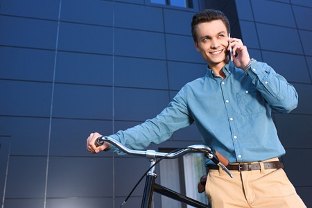 low angle view of smiling young man standing with bike and talking by smartphone