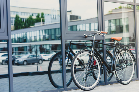 stylish bicycle reflected in modern building on empty street Stock fotó