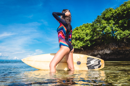 side view of woman in wetsuit with surfboard posing in ocean at Nusa dua Beach, Bali, Indonesia