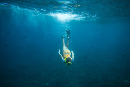 underwater photo of woman in fins, diving mask and snorkel diving alone in ocean Banque d'images