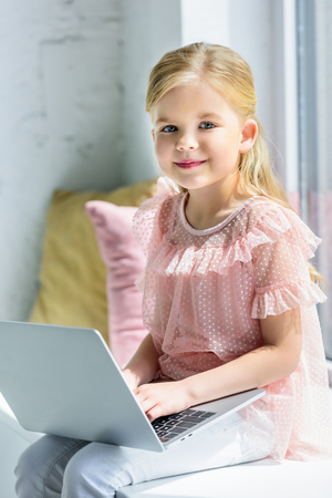 adorable child using laptop and smiling at camera at home 版權商用圖片 - 105987310