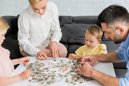 cropped shot of happy family playing with puzzle pieces at home Stock Photo