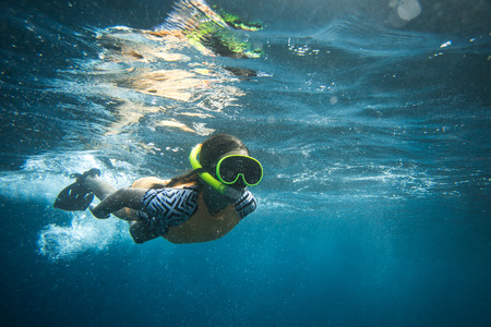 underwater photo of woman in diving mask and snorkel diving alone in ocean Stock Photo