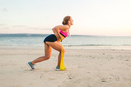 side view of sportswoman doing exercise with stretching band on beach Stock Photo