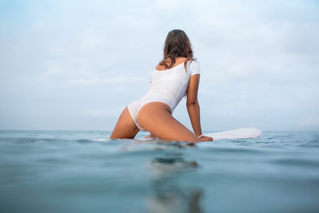 rear view of seductive young woman in wet white swimsuit sitting on surfboard in ocean