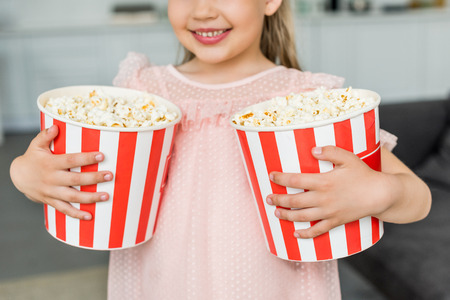 cropped shot of cute smiling child holding popcorn boxes at home