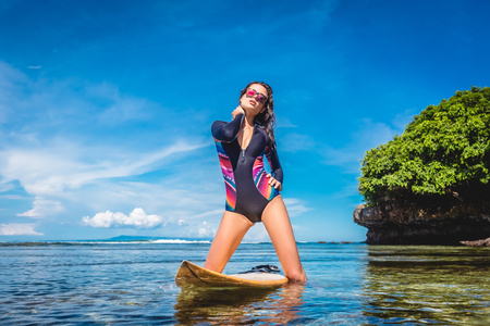 attractive woman in wetsuit and sunglasses with surfboard posing in ocean at Nusa dua Beach, Bali, Indonesia Stock Photo - 106992807