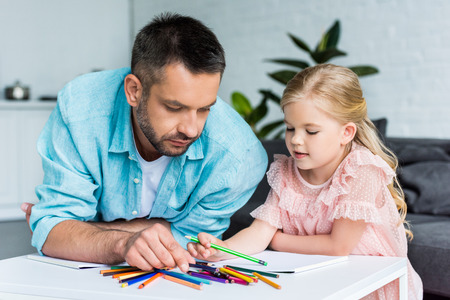 father and daughter drawing with colored pencils together at home 版權商用圖片