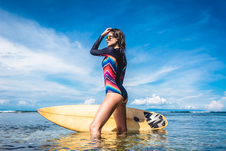 attractive young woman in wetsuit and sunglasses with surfboard posing in ocean at Nusa dua Beach, Bali, Indonesia Stock Photo