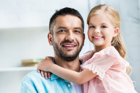 happy father and daughter hugging and smiling at camera 版權商用圖片