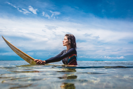 side view of young sportswoman in wetsuit on surfing board in ocean at Nusa dua Beach, Bali, Indonesia