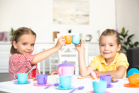 cute little sisters clinking toy cups while pretending to have tea party together at home 版權商用圖片