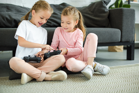 little sisters with gamepads playing video game together at home Stock fotó