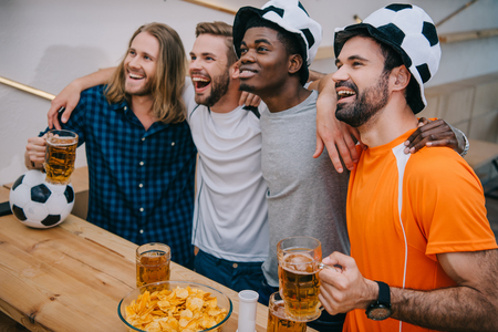 excited multicultural group of male football fans in soccer ball hats holding beer and watching soccer match at bar