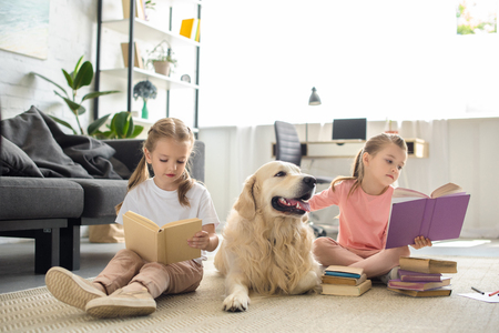 cute little sisters reading books with golden retriever dog near by at home