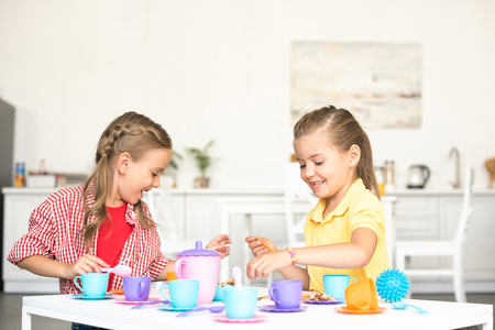 cute little sisters pretending to have tea party together at home