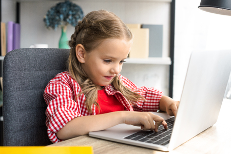 side view of little kid using laptop at table at home Stock fotó