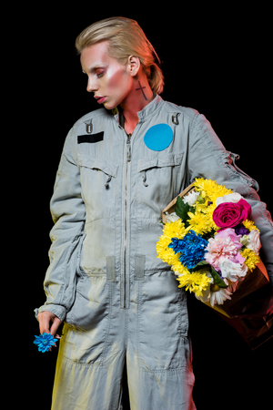 attractive female astronaut posing in spacesuit with colorful flowers in paper bag, isolated on black Stock Photo