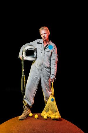 attractive cosmonaut in spacesuit with helmet and lemons in string bag posing on mars