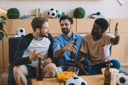 gesturing multicultural friends talking during watch of soccer match at home Stockfoto