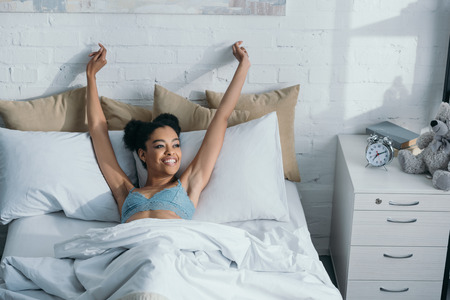 smiling african american girl waking up and stretching in bed Banco de Imagens - 106416947
