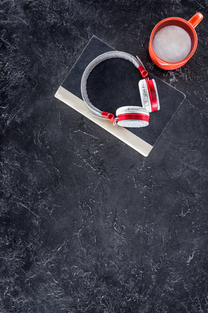 top view of book, headphones and red cup on grey tabletop Stock Photo