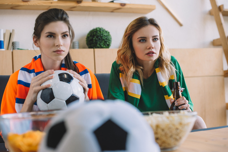 focused female football fans in different t-shirt and scarfs watching soccer match at home