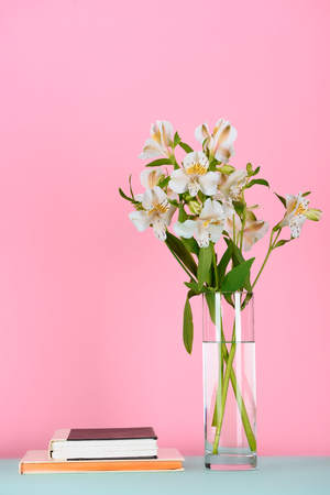 two books and bouquet of alstroemeria flowers on table on pink Stock Photo