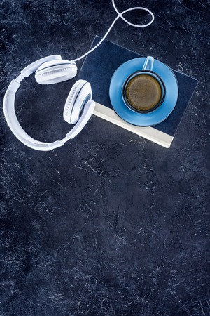 top view of book, white headphones and blue cup with coffee on grey tabletop Banque d'images - 107015311