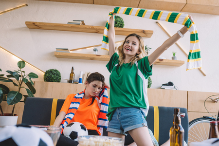 young smiling woman in green fan t-shirt celebrating victory and holding scarf over head while her upset female friend in orange t-shirt sitting behind during watch of soccer match at home