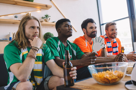 group of multicultural male friends in green and orange fan t-shirts watching soccer match near table with chips and popcorn at home Stockfoto