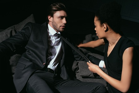young multiracial couple in black clothing on sofa on dark background