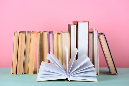 open book in front of row of books on table on pink Stock Photo