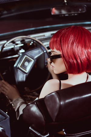 young woman in red wig and sunglasses driving retro car