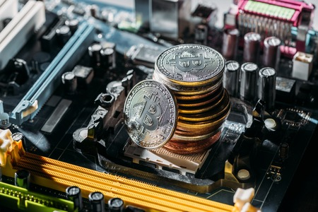 close up view of pile of bitcoins on computer motherboard
