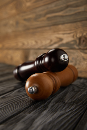 wooden pepper grinder and salt grinder on wooden floor