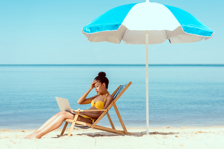 side view of smiling african american female freelancer sitting on deck chair and using laptop under beach umbrella in front of sea Stock Photo