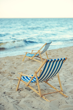 selective focus of wooden beach chairs on sandy beach with sea on background Stock Photo